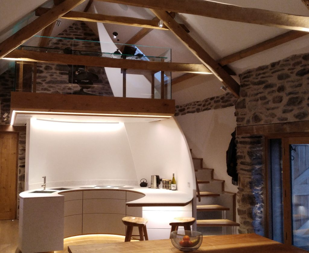 curved kitchen below oak mezzanine